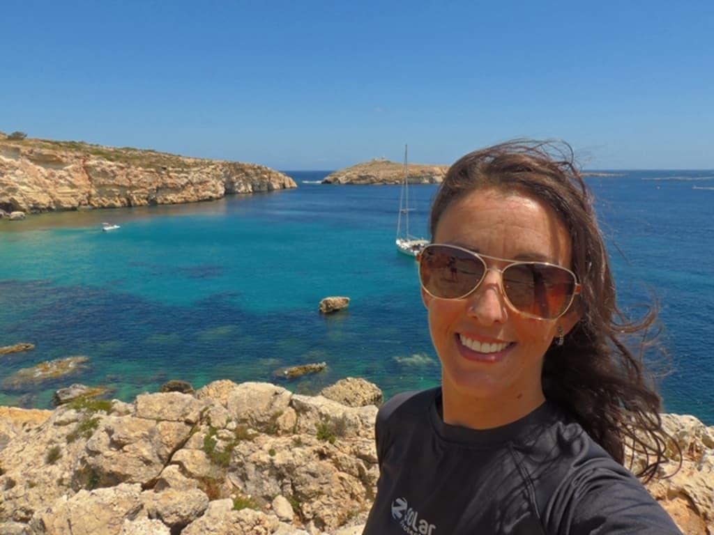 viajera en playa en Malta donde puedes viajar para aprender ingles