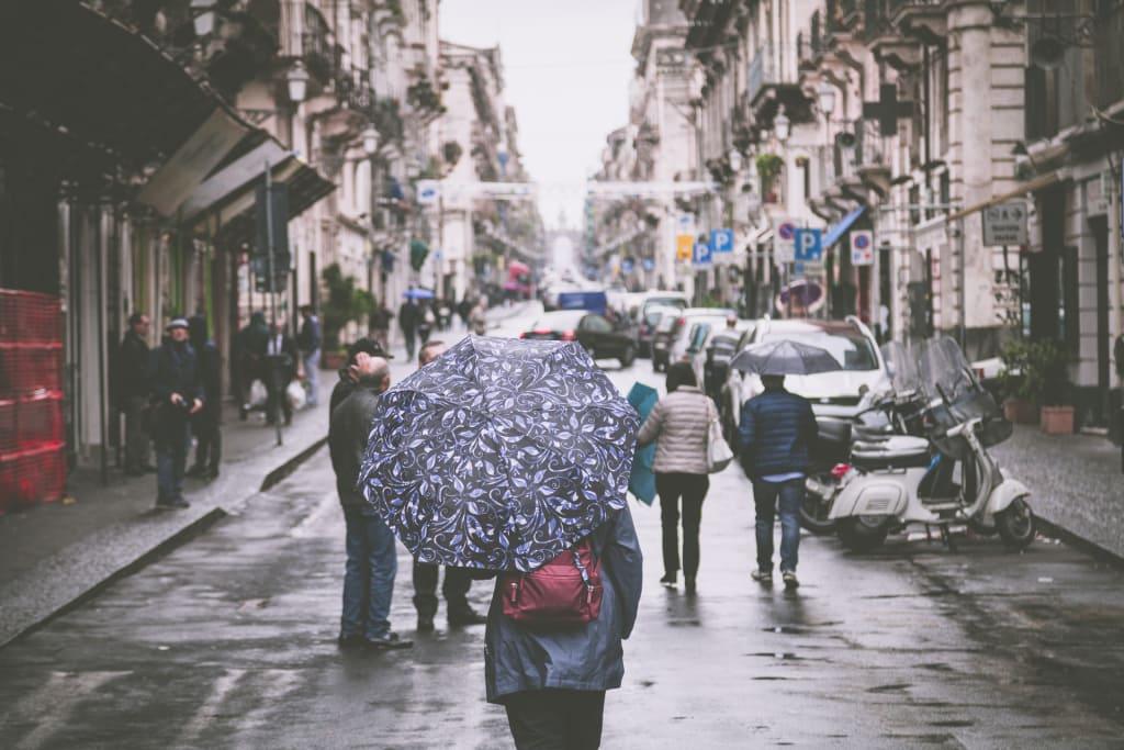 mulher conhecendo a cidade a pé com guarda chuva