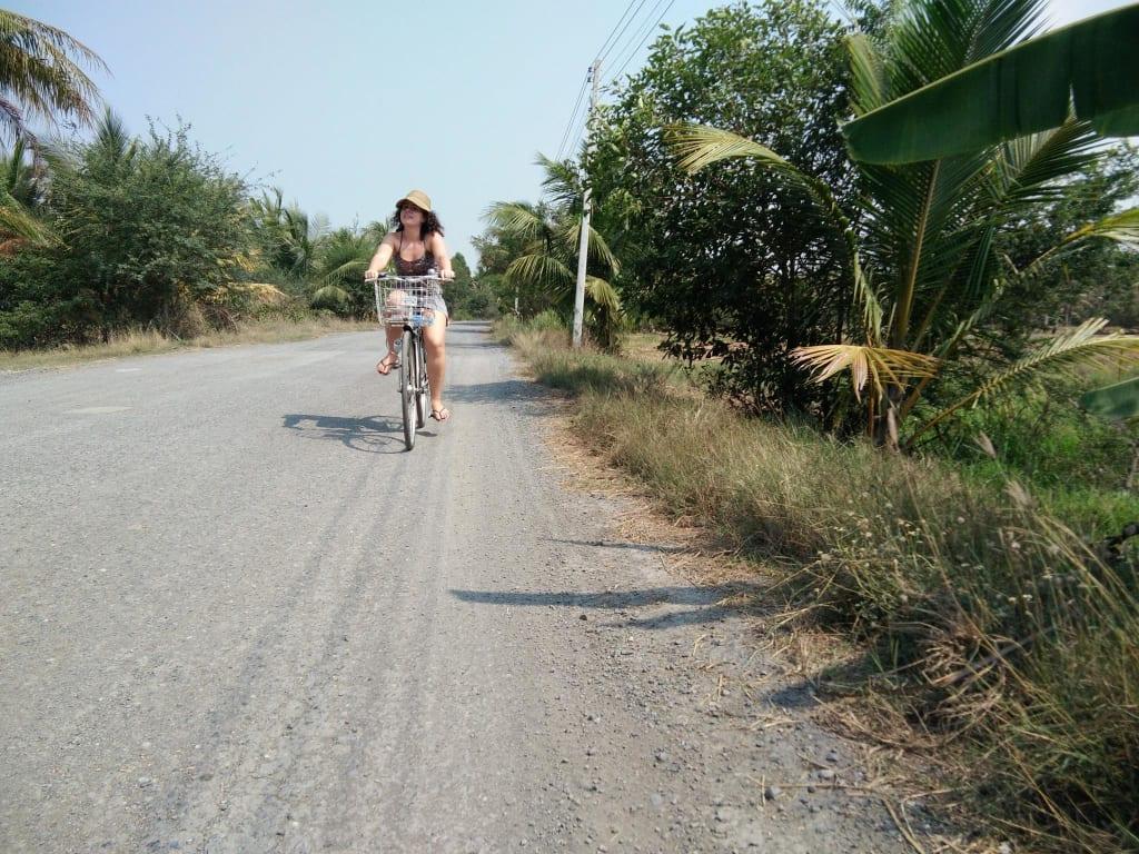 voluntária worldpackers andando de bicicleta na área rural da Tailândia
