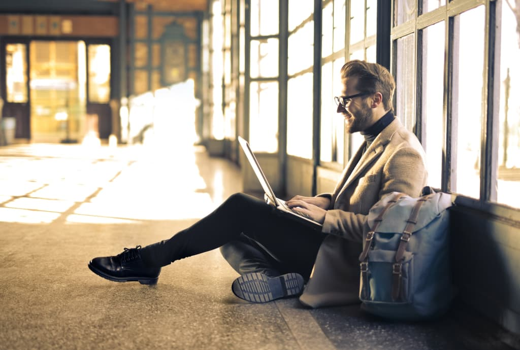 Imagem de homem sentado no chão e encostado em uma parede com janelas usando o computador ao seu colo