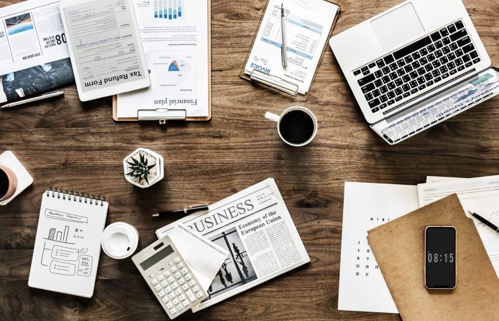 mesa de escritório com notebook, caderno de anotaçoes e planilhas
