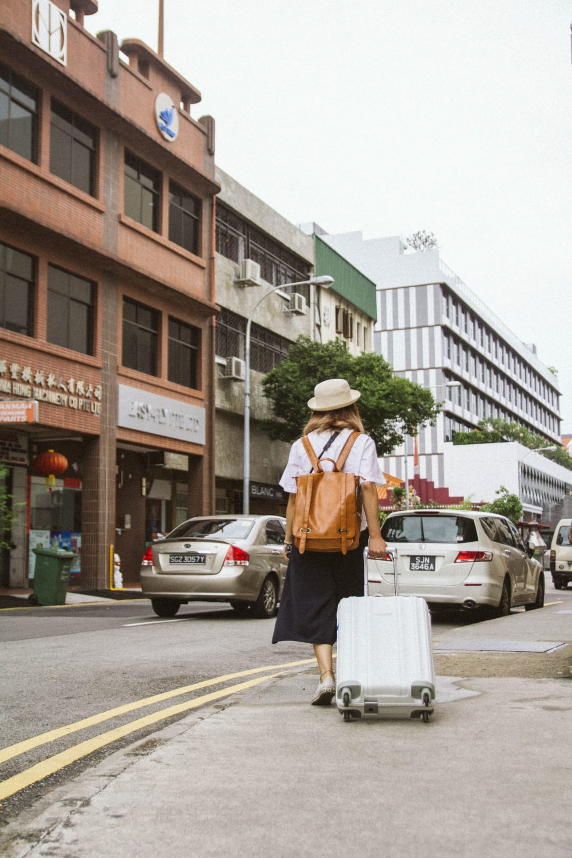 Woman strolling down the sidewalk with minimalist luggage