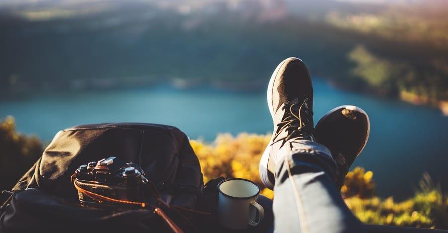 Imagem de pés, uma mochila e uma câmera e ao fundo a paisagem de um lago