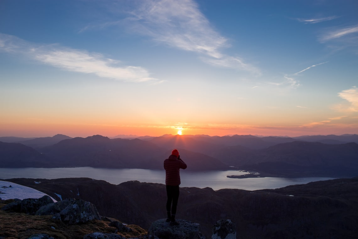 Solo traveler photographing a mountain sunrise