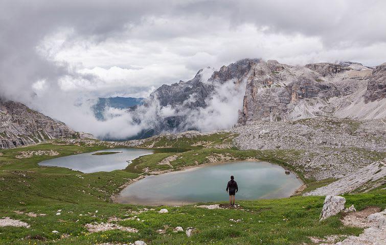 7 Razones por las que viajar barato mejora tu viaje - Worldpackers - hombre viajero en dolomitas italia