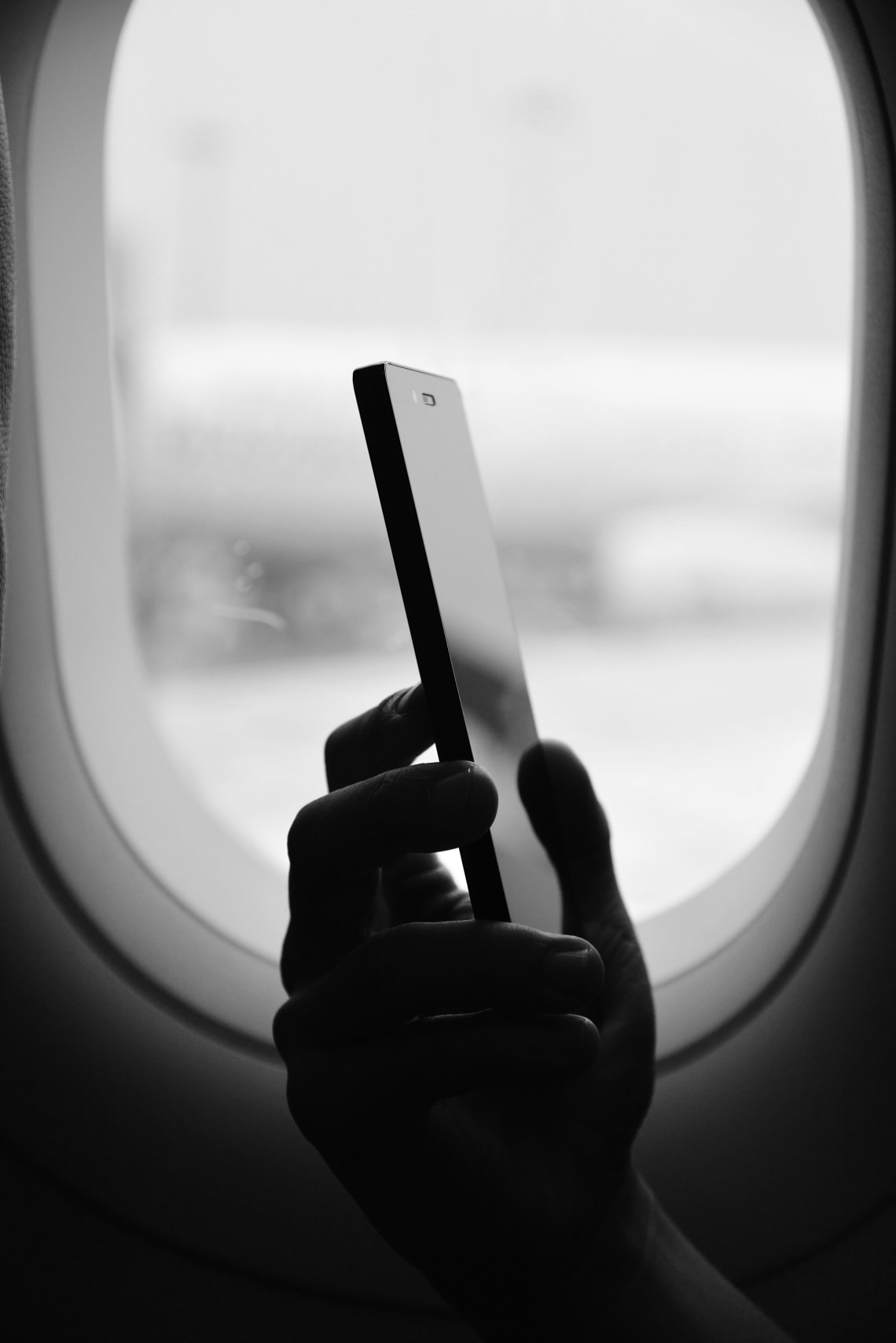 Smartphone in front of airplane window