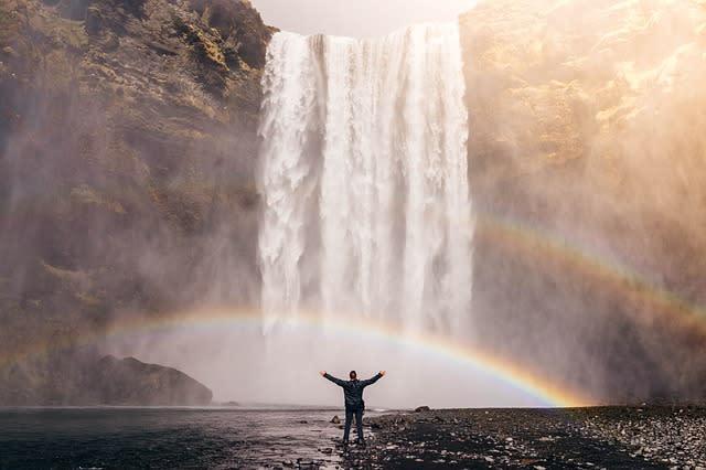 Imagem de turista em uma cachoeira com arco iris. Para diminuir os gastos de viagem, opte por passeios gratuitos