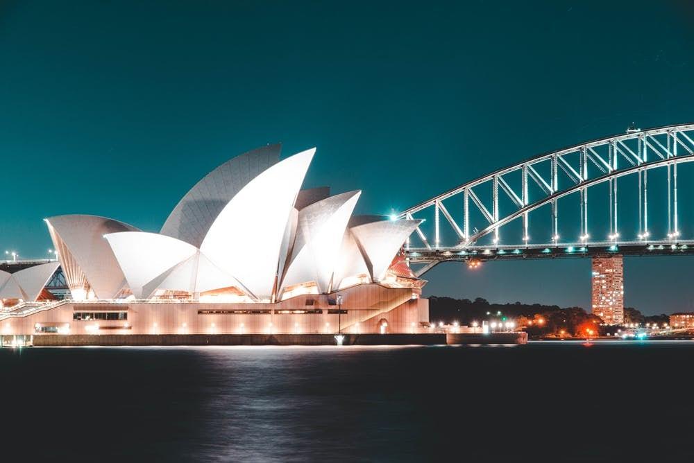 Cómo viajar barato por Australia: itinerarios, consejos y demás - Worldpackers - casa de la Opera de Sydney con puente y de noche