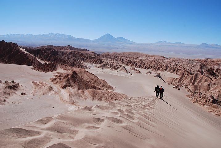 Cómo viajar por el norte de Chile con bajo presupuesto - Worldpackers - viajeros caminando en dunas desierto de Atacama