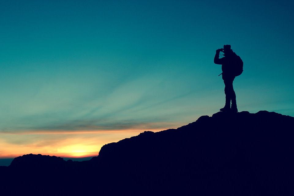 Viajar por Sudamérica solo: todo lo que debes saber - Worldpackers - viajero con mochila sobre una montaña mirando el atardecer