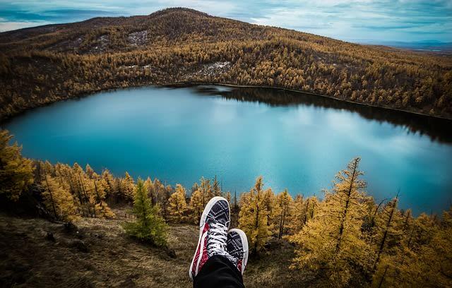 Imagem de pés e um lago e muitas árvores ao fundo