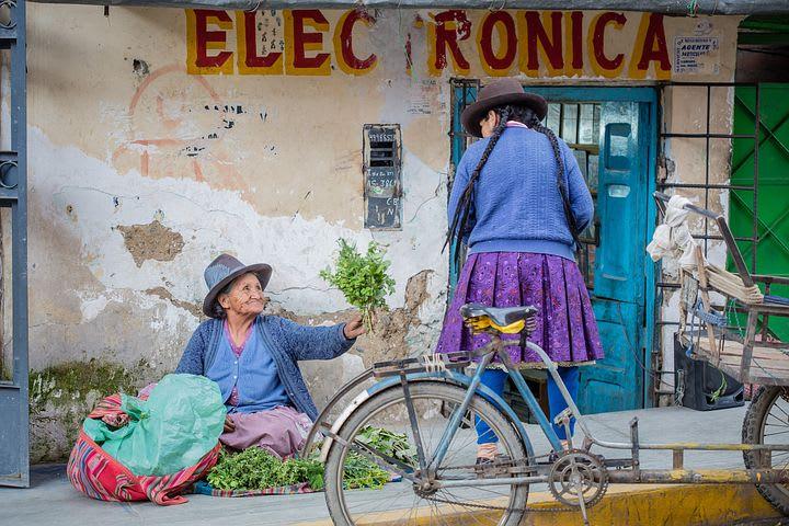 Cómo armar un presupuesto para viajar a Perú como mochilero - Worldpackers - cholitas sentadas en un andén