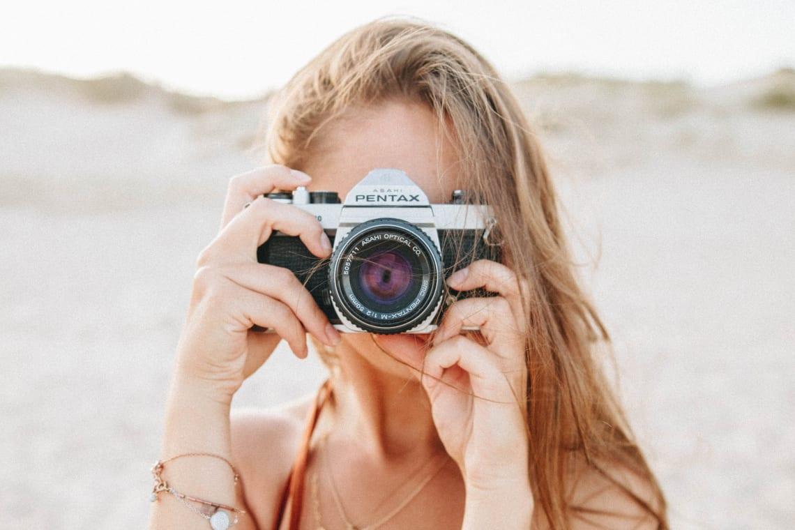 Woman taking a photograph, Tarifa, Spain