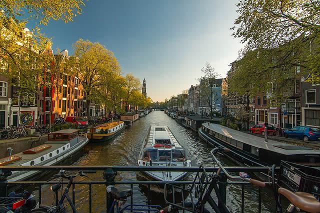Imagem de barcos passando pelo rio de atravessa a cidade de Amsterdã