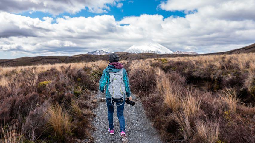 Cómo elegir una mochila de viaje - Worldpackers - mujer caminando con mochila y cámara en mano