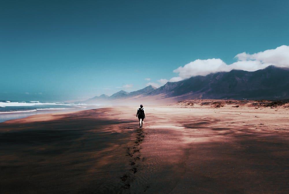 Lo que debes saber para enfrentar tu miedo a viajar sola - worldpackers - mujer caminando sola en la playa