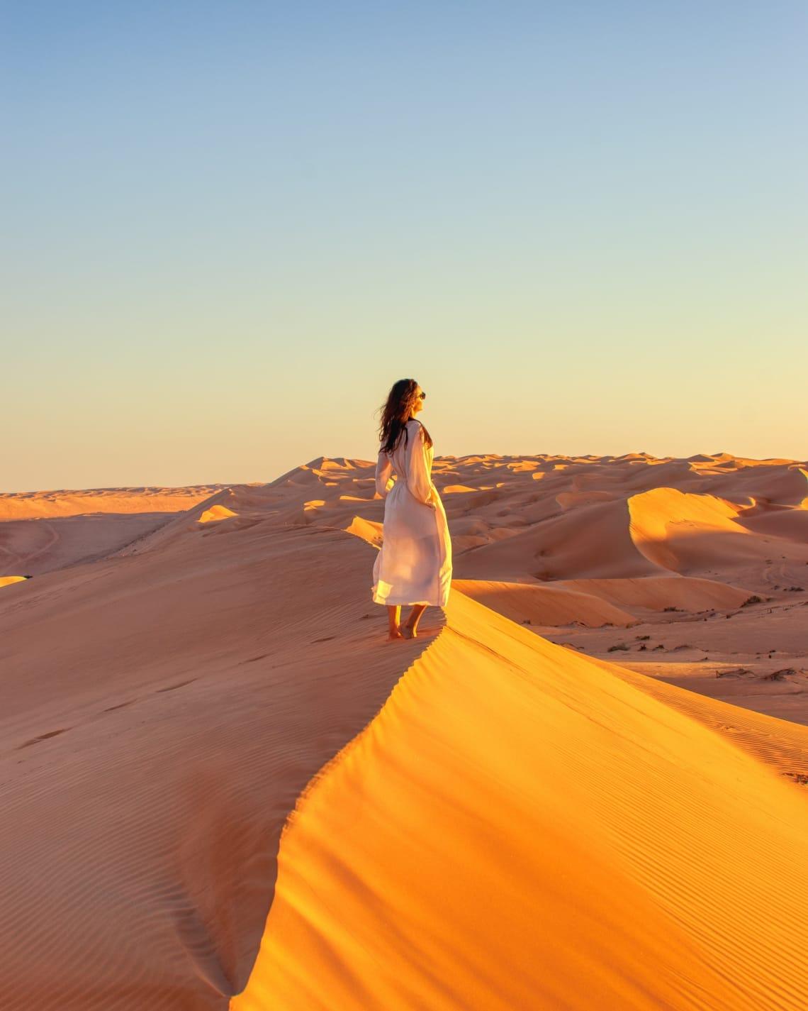 Solo female traveler watching a desert sunset