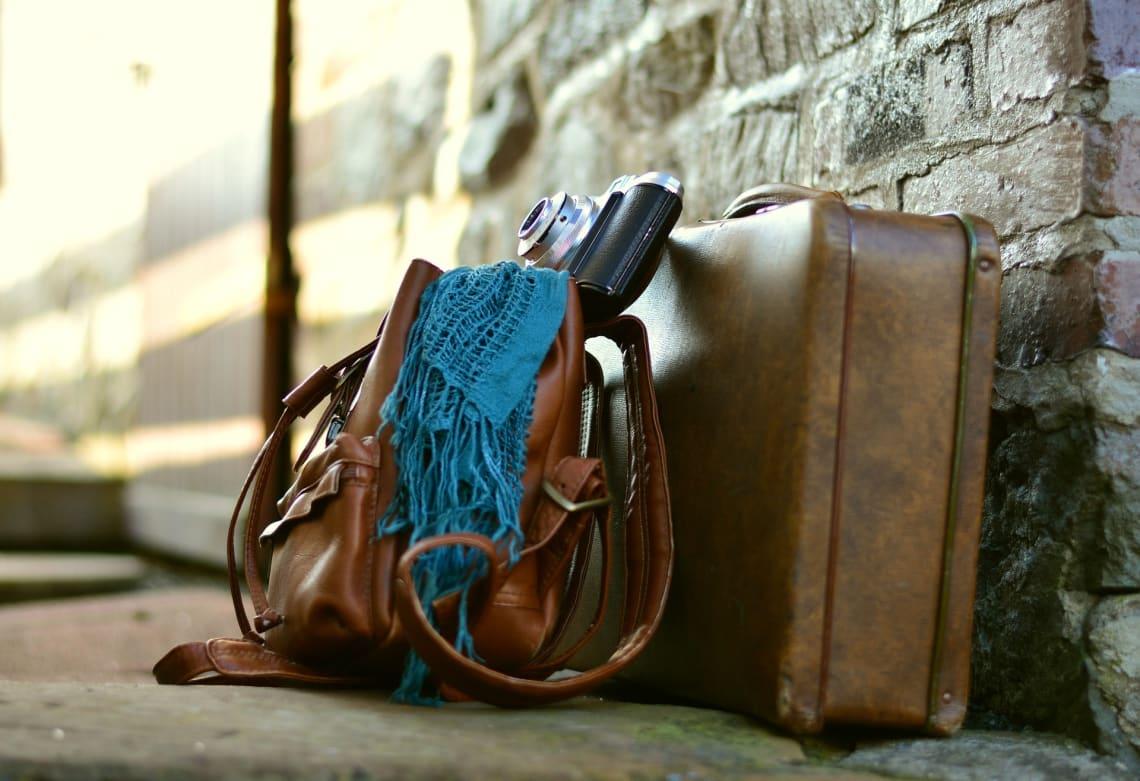 Stylish suitcase, day bag, and camera