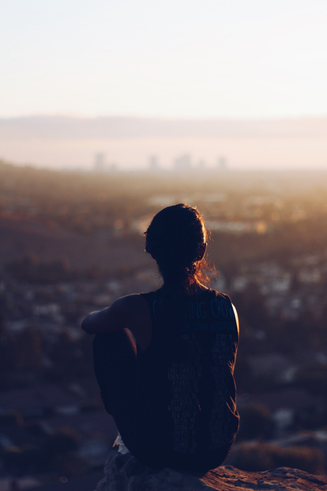 Solo female traveler enjoying a beautiful sunset from an overlook