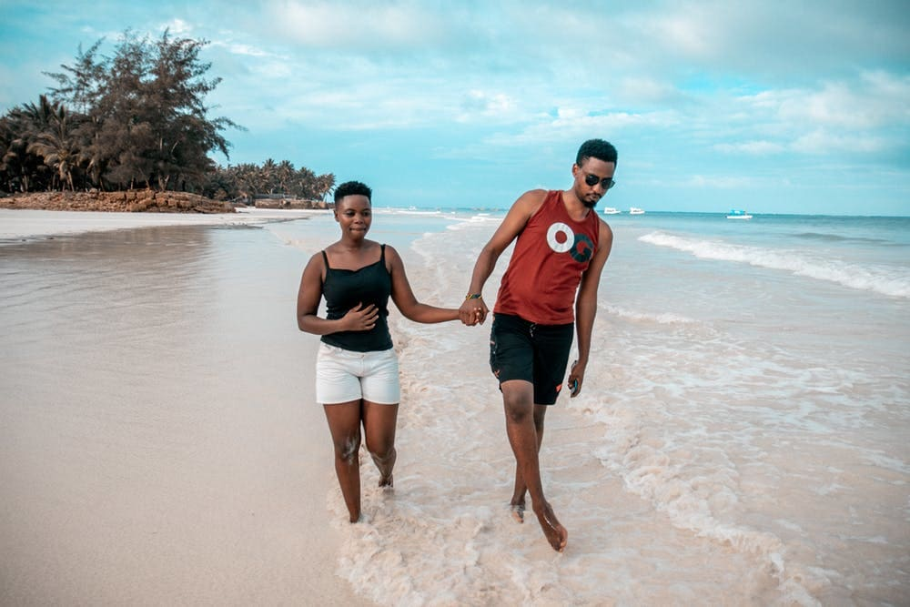 6 Lugares para viajar en pareja por Sudamérica y hacer voluntariados - Worldpackers - pareja en playa con mar azul claro