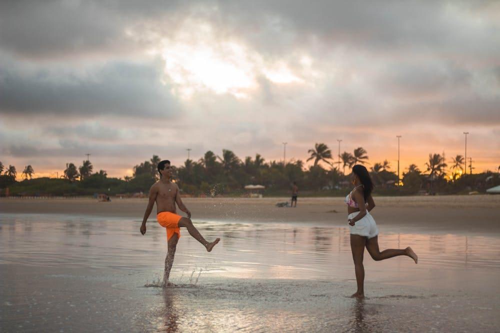 6 Lugares para viajar en pareja por Sudamérica y hacer voluntariados - Worldpackers - pareja jugando sobre la playa