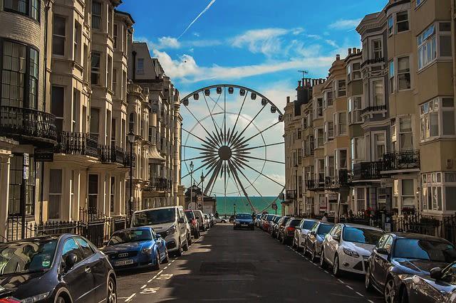 Foto de rua em Brighton e ao fundo o mar e uma roda gigante, ótimo destino para uma viagem lgbt