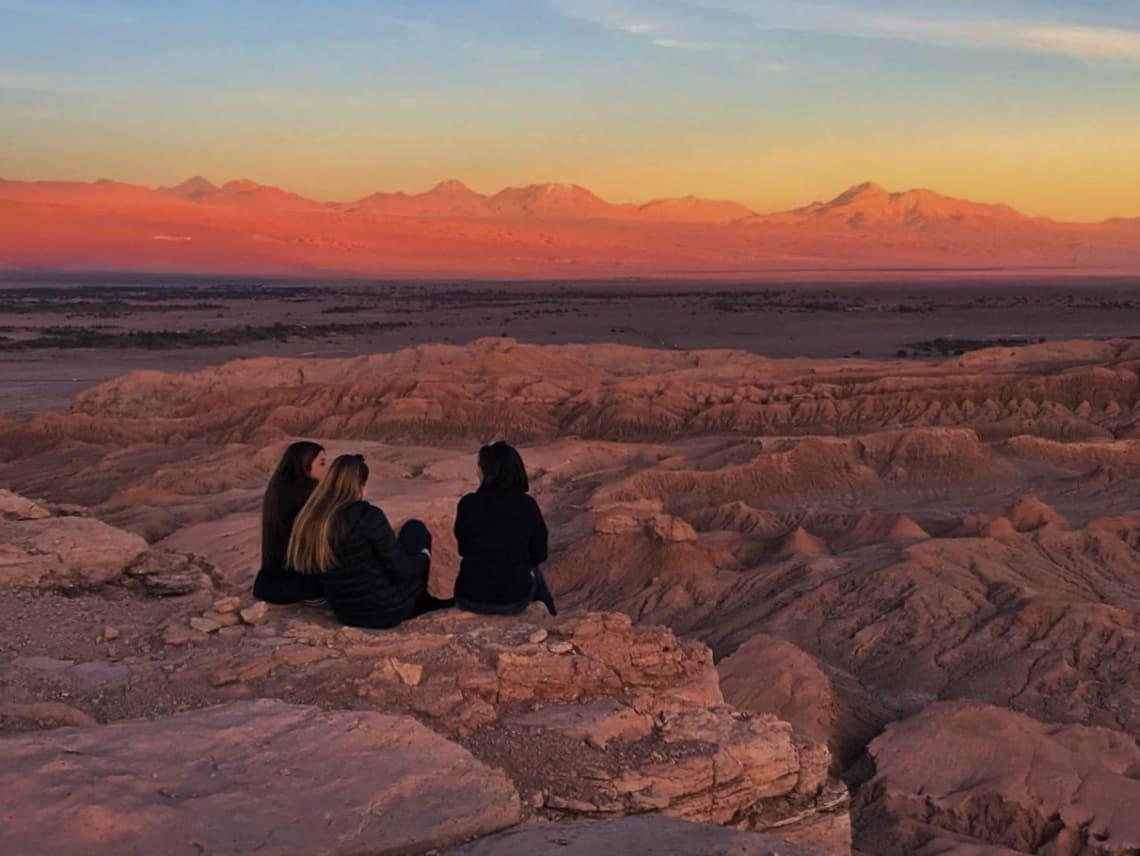 Viajar sola no es estar realmente sola - Worldpackers - mujeres viajeras en una montaña viendo el atardecer