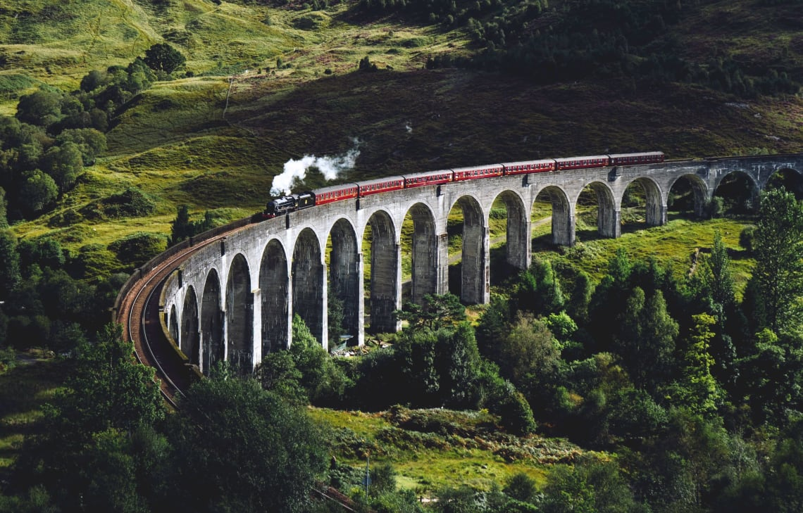 Train passing through a vast green landscape, UK