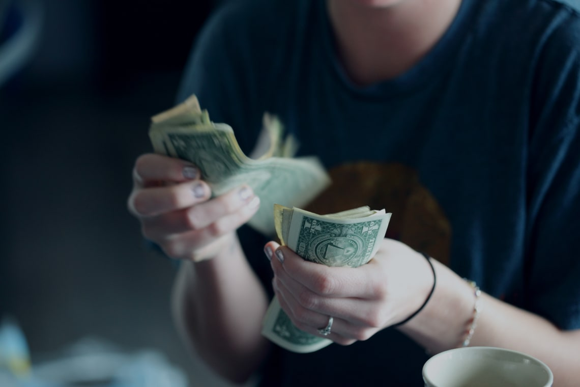 Mulher contando dinheiro em espécie ao levar para o exterior