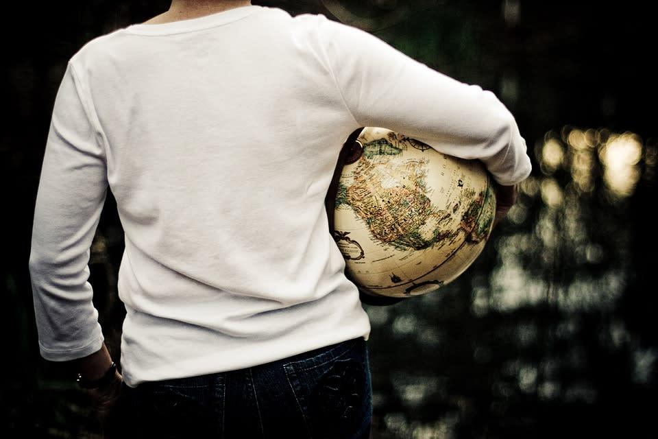 10 ventajas de vivir una aventura en el extranjero - Worldpackers - mujer sosteniendo el globo terráqueo