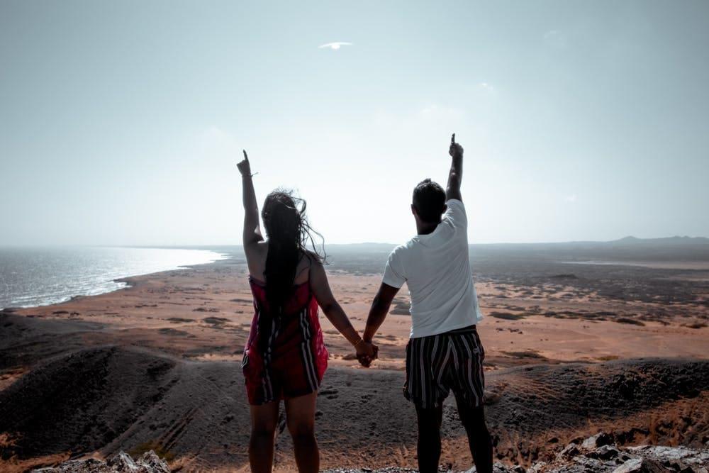 Secretos del camino: 10 consejos para viajar en pareja por largo tiempo - Worldpackers - pareja con los brazos arriba mirando hacia el mar