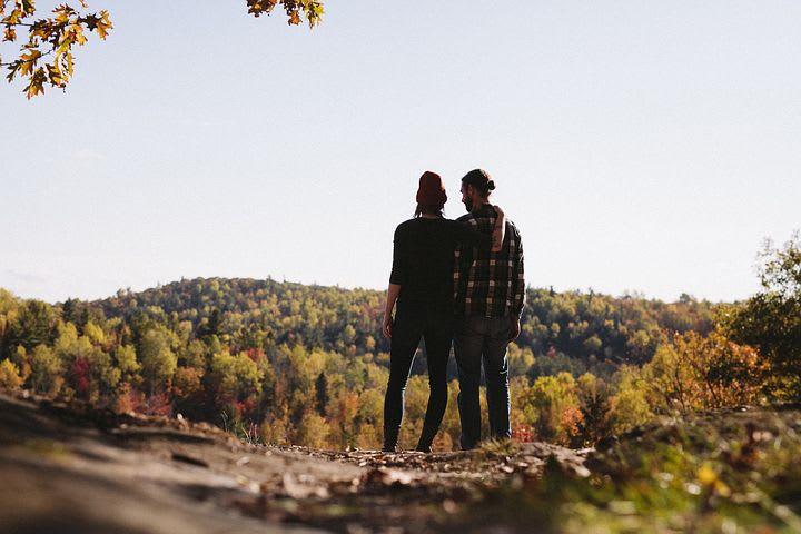 Secretos del camino: 10 consejos para viajar en pareja por largo tiempo - Worldpackers - pareja mirando la cima de la montaña durante el otoño