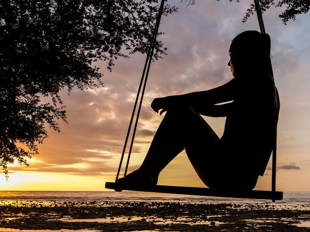Qué es y cómo lograr el Slow Traveling - Worldpackers - mujer en columpio viendo el atardecer