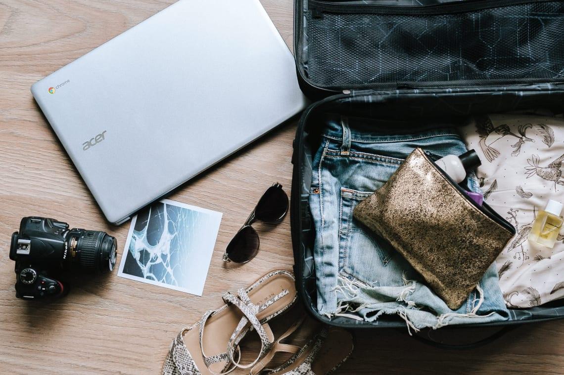 Bagagem de mão com algumas roupas, sapatos, câmera e computador
