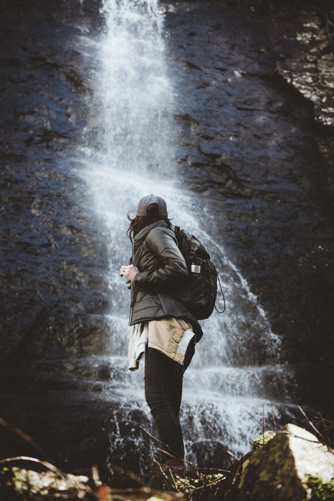 Solo female traveler standing in front of a waterfall
