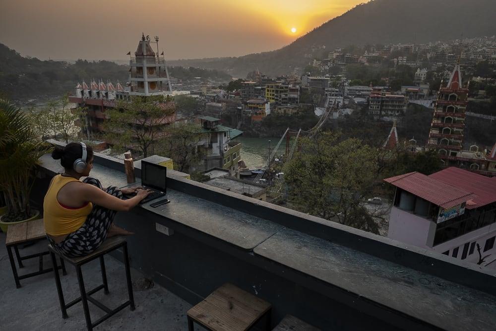 17 días haciendo un voluntariado en India, en la capital mundial del yoga: Rishikesh - Worldpackers - viajera en terraza de un hostal, trabajando durante el atardecer en India