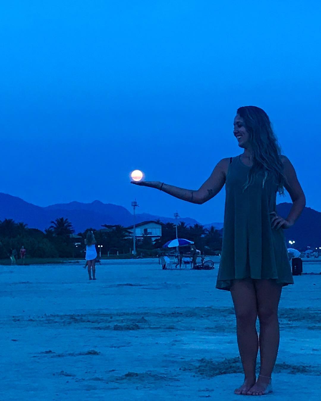 Imagem da Jéssica em uma praia e ao fundo a lua cheia