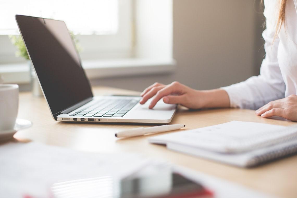 Mulher pesquisando em seu computador e caderno de anotações ao lado