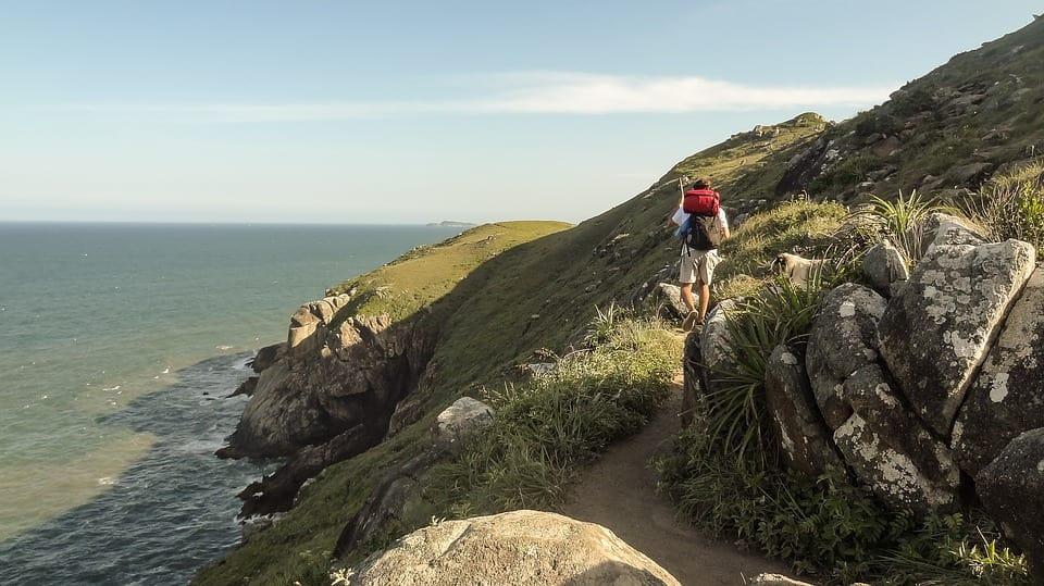turista caminhando pelas pedras de Floripa