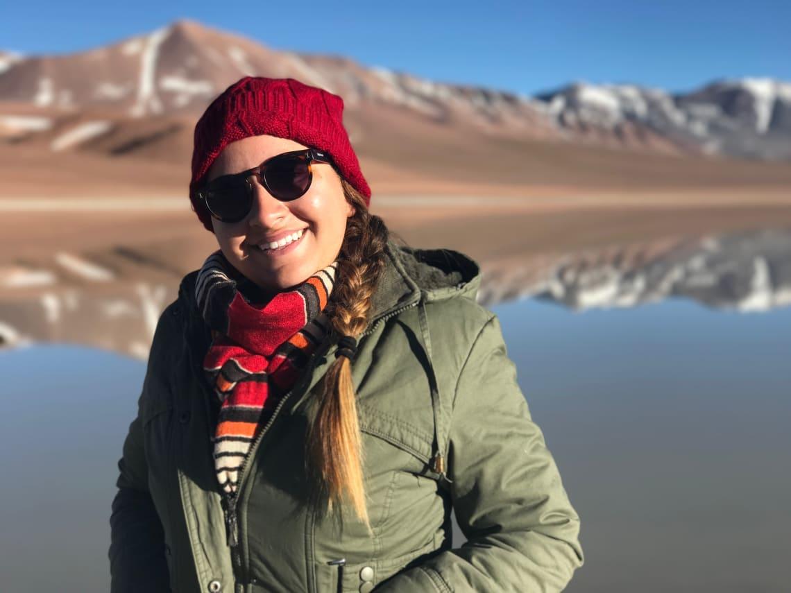 Imagem de uma mulher com jaqueta e gorro em primeiro plano e ao fundo uma cordilheira