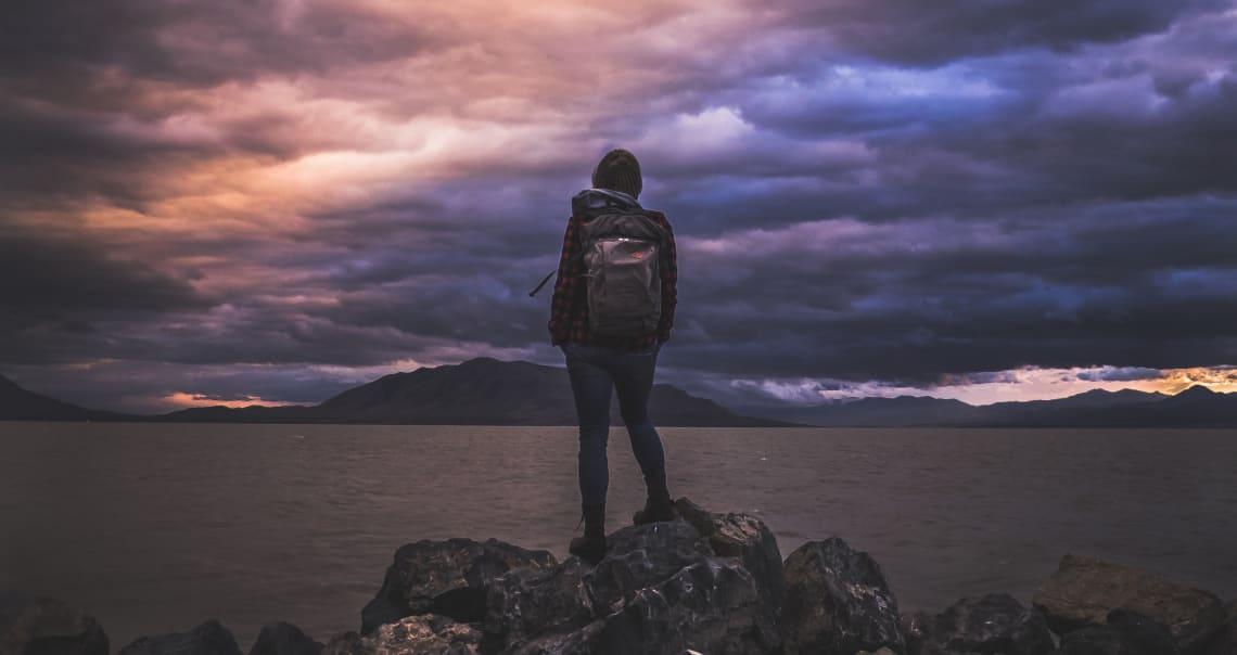 mulher sobre pedras vendo um lago