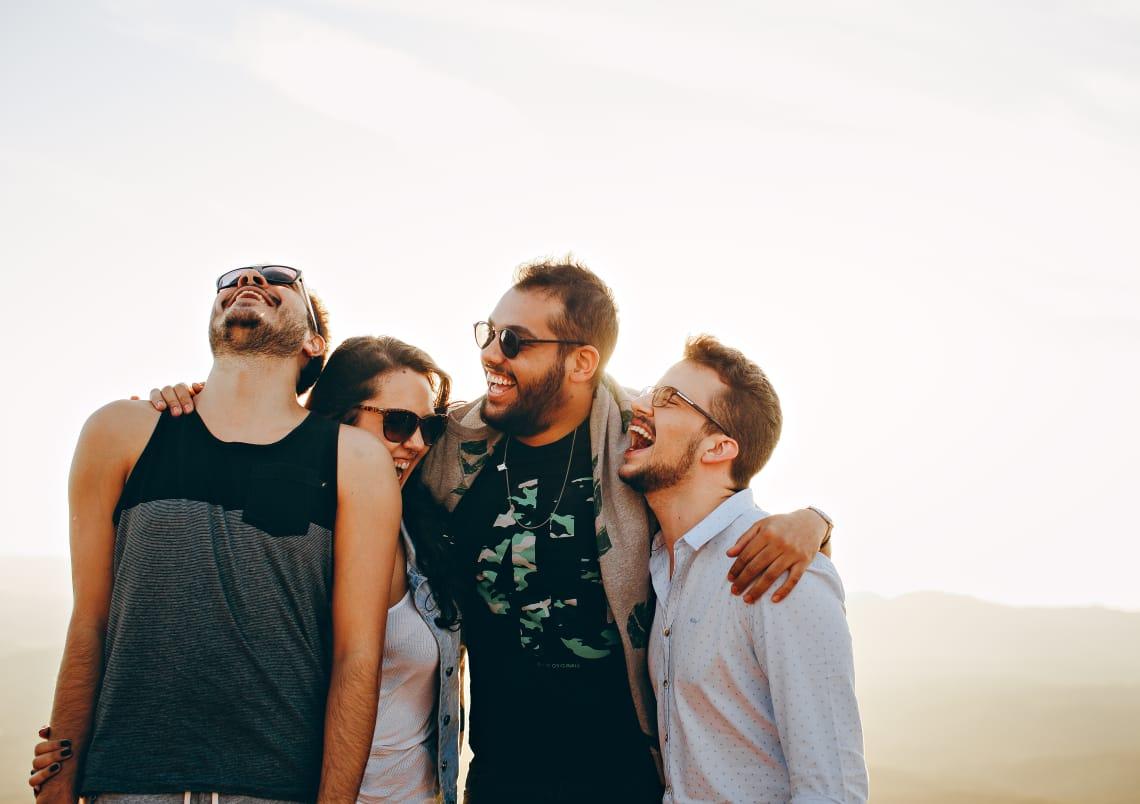grupo de quatro amigos sorrindo e aproveitando o tempo livre