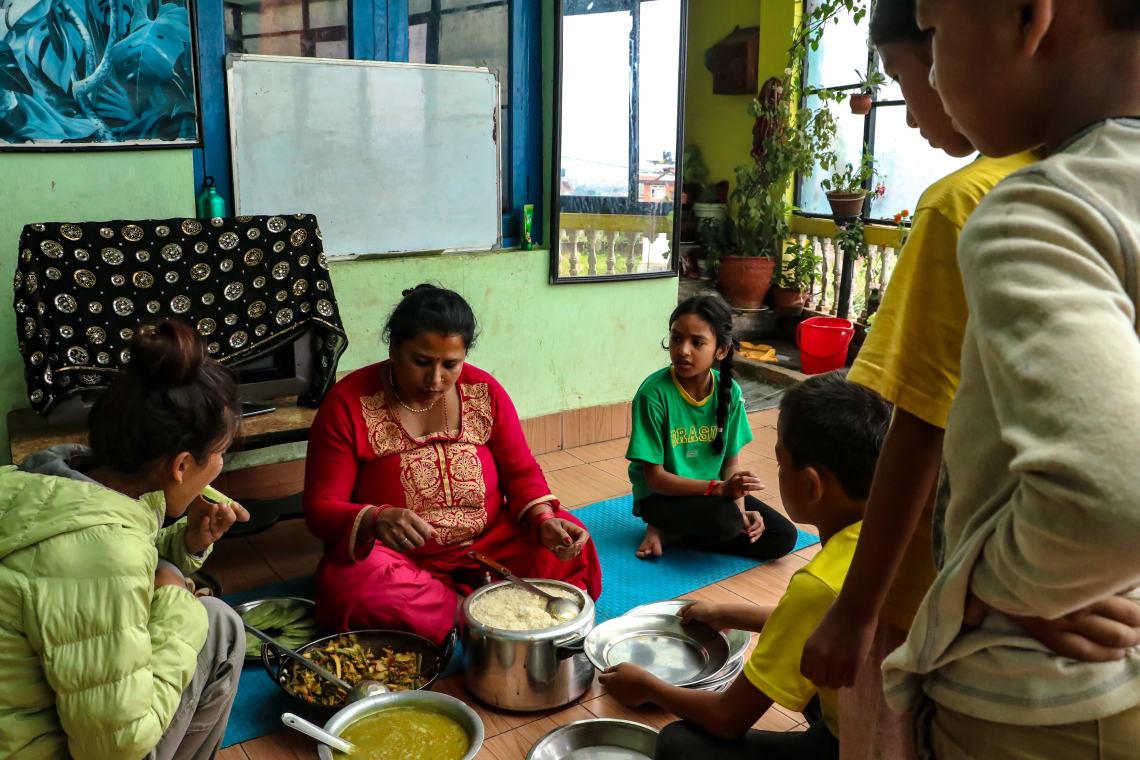 Haciendo un voluntariado en Nepal como profesora - Worldpackers - familia en Nepal comiendo en el piso