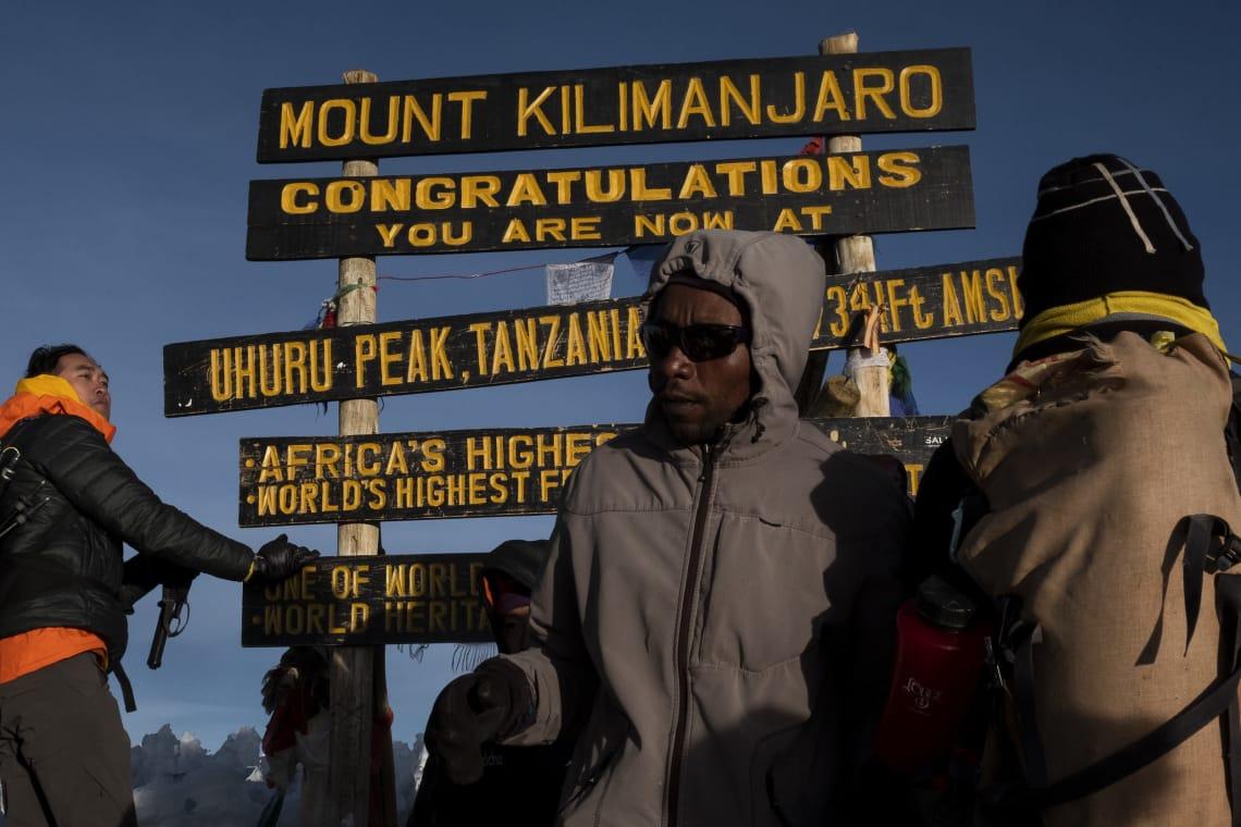 Kilimanjaro: hacer el trekking más alto de África - Worldpackers - porteadores y viajeros en la cima del Kilimanjaro en Uhuru