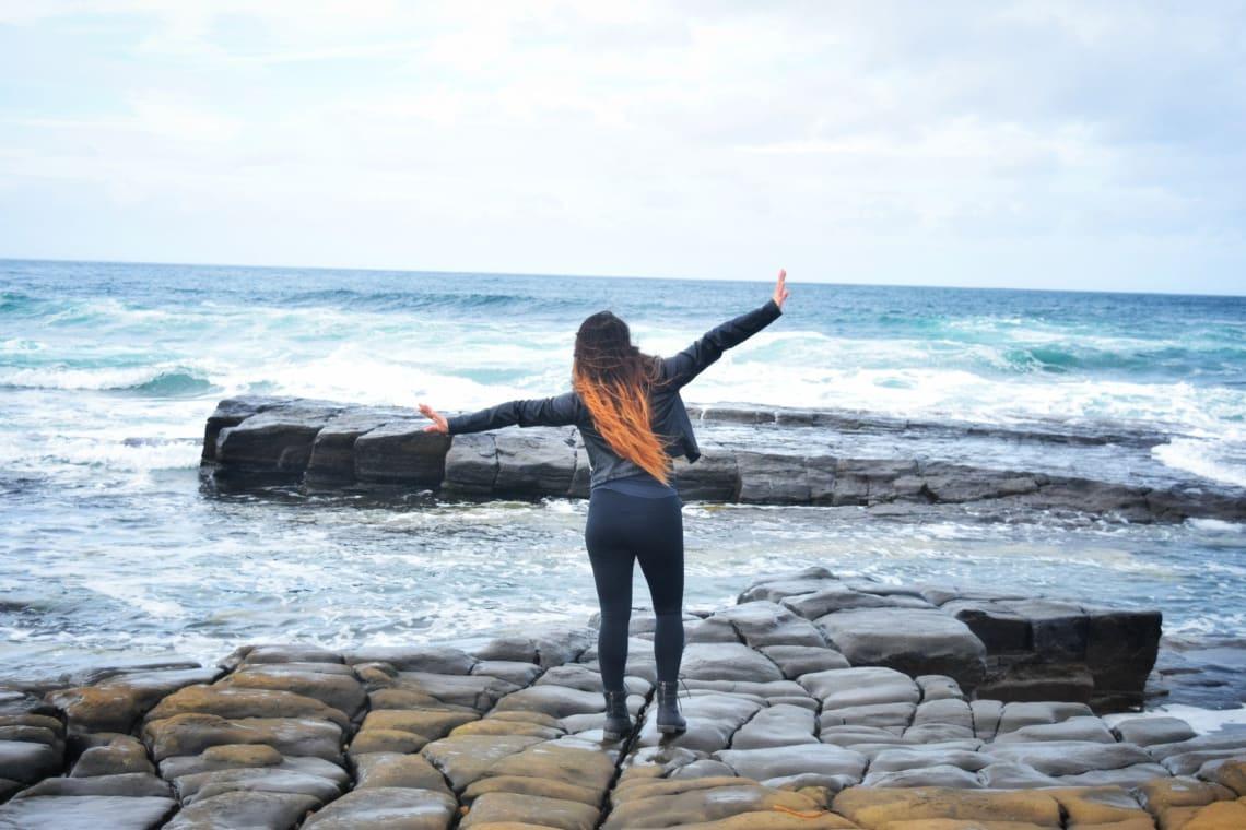 Solo female traveler enjoying the ocean breeze