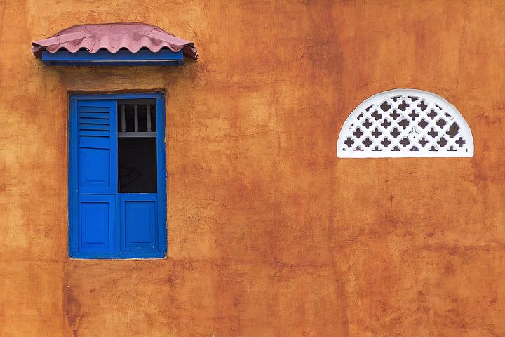 10 cosas que puedes hacer en Cartagena con poco dinero - Worldpackers - fachada de pared colorida con ventana azul en cartagena