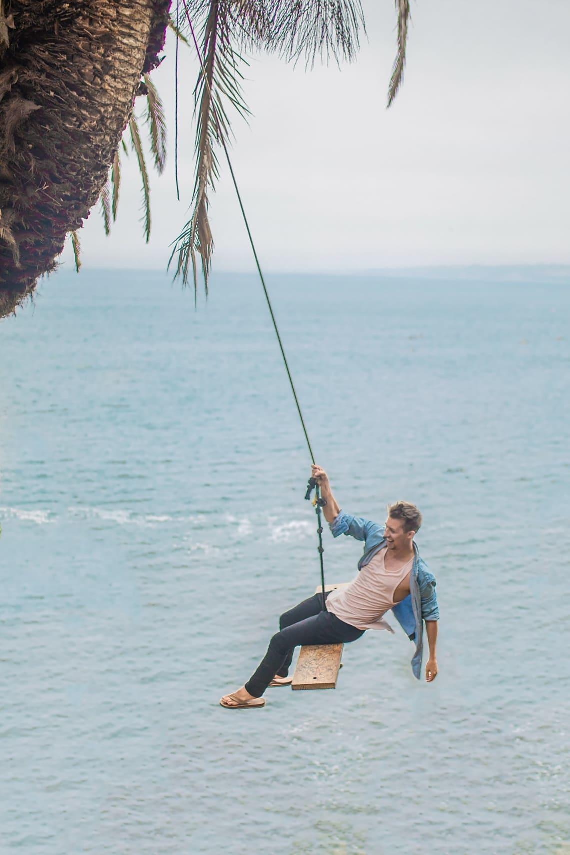 Happy solo traveler swinging over the ocean