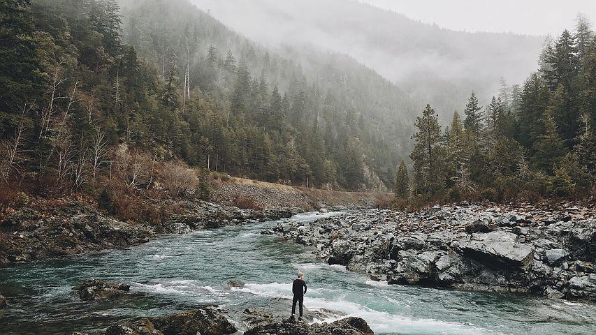 7 Razones por las que viajar barato mejora tu viaje - Worldpackers - viajero viendo la montaña desde el rio