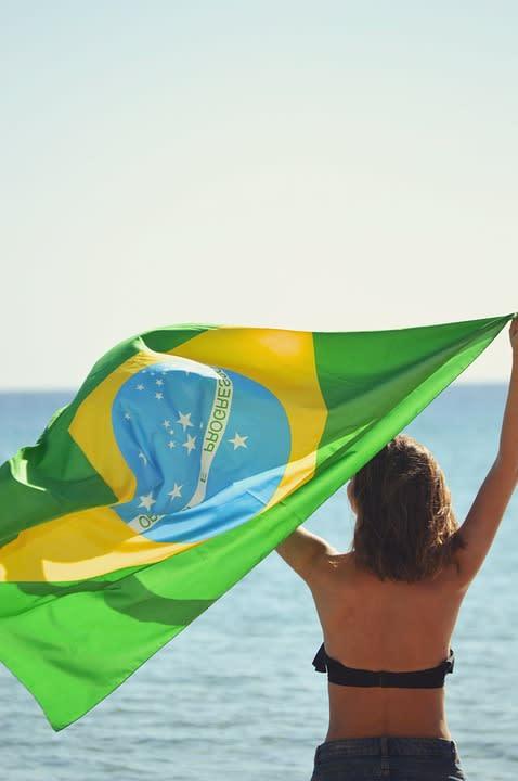 Viajar por Sudamérica solo: todo lo que debes saber - Worldpackers - mujer sosteniendo la bandera de Brasil y mirando hacia la playa