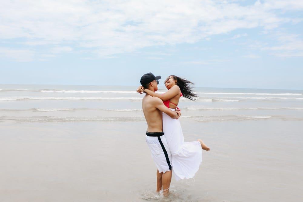 6 Lugares para viajar en pareja por Sudamérica y hacer voluntariados - Worldpackers - hombre sosteniendo en brazos a una mujer sobre la playa
